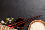 Japanese sushi chopsticks, soy sauce bowl, rice and sakura bloss