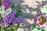 Coffee cup and colorful lilac flowers on garden table