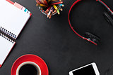 Desk with notepad, coffee, smartphone and headphones