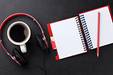 Desk with notepad, coffee and headphones