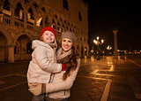 Mother and child standing on Piazza San Marco in the evening