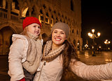 Mother with child taking selfie on Piazza San Marco in Venice
