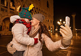 Mother and child hugging while taking selfie on Piazza San Marco