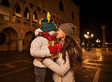 Happy mother hugging child with Christmas gift box in Venice