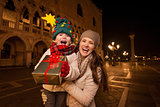 Happy mother and child showing Christmas gift box in Venice