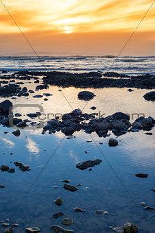 beautiful mellow sunset over rocky beach
