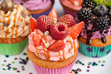 Delicious cupcake decorated with raspberry and strawberry