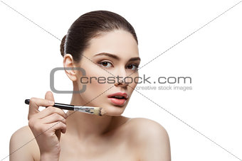 Beautiful girl applying foundation with brush
