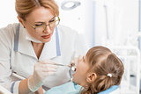 dentist woman examining kid patient in office