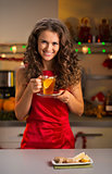 Woman having cup of ginger tea in christmas decorated kitchen