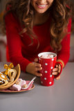 Woman having cup of hot chocolate and Christmas sweets. Closeup