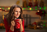 Woman having cup of hot chocolate in Christmas decorated kitchen