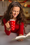 Woman with cup of chocolate and book in Christmas kitchen