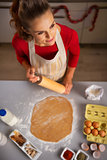Housewife with rolling pin cooking Christmas cookie in kitchen