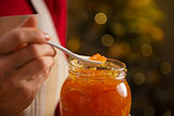 Closeup on a spoon of homemade marmalade in hand of housewife