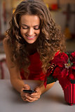Happy young woman in red dress writing sms in Christmas kitchen