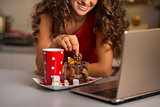 Woman having cup of hot chocolate with cookies and using laptop