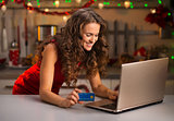 Woman with credit card typing on laptop in Christmas kitchen