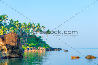 a large boulder in a calm sea and palm trees