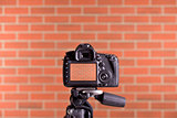 DSLR Camera on tripod shooting brick wall