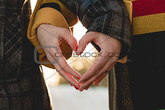 bride and groom holding hands in shape of heart