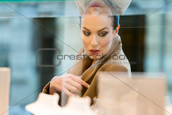 beautiful woman looking for sale on window shop