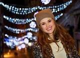 Woman standing in the front of Christmas lights in the evening