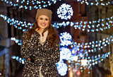 Happy woman standing in front of Christmas lights in evening