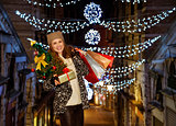 Portrait of woman with Christmas tree, gift and shopping bags