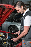 Mechanic using a tablet pc at the repair garage