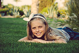 Beautiful, happy, young girl lying on the grass.