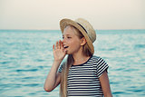 Young girl in a straw hat on the sea is calling someone