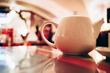 White teapot at restaurant close up.