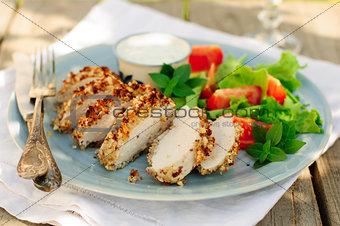 Sliced peanut crusted chicken breast with fresh salad