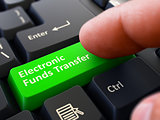 Pressing Green Button Electronic Funds Transfer on Black Keyboar