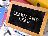 Learn and Lead - Chalkboard with Motivation Quote.