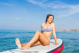 Woman sitting over a paddle surfboard