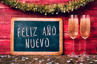 champagne and text feliz ano nuevo, happy new year in spanish