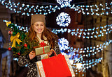 Young woman with gift and shopping bags among Christmas lights
