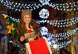 Young woman with gift and shopping bags among Christmas lights