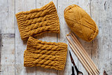 wool yellow legwarmers, scissors, knitting needles and yarn