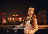Smiling young woman standing on a bridge overlooking Grand canal