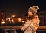 Seen from behind, woman on bridge looking on Grand canal