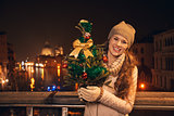 Young woman with Christmas tree standing on a bridge in Venice