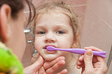 Mom helping girl brushing teeth