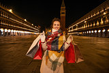 Woman in winter coat holding shopping bags on Piazza San Marco