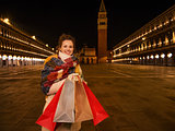 Smiling woman with shopping bags on Piazza San Marco in Venice