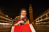 Smiling woman with shopping bags on Piazza San Marco in evening