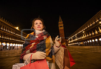 Modern woman with shopping bags on Piazza San Marco in evening