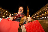 Woman with shopping bags showing thumbs up on Piazza San Marco
